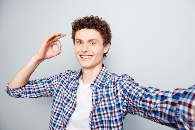 若い男が灰色に分離されたselfie写真を撮影okサインを表示