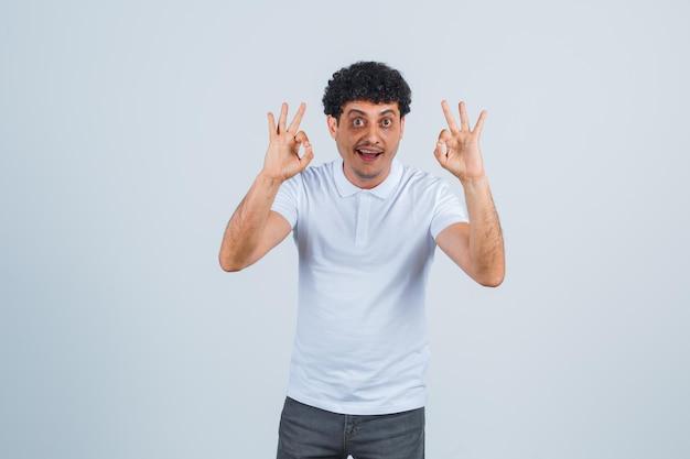 Молодой человек показывает хорошие знаки в белой футболке и джинсах и выглядит счастливым, вид спереди.