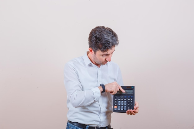 Young man showing outcome on calculator in white shirt, jeans front view.