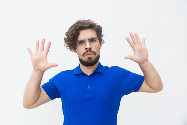 Young man showing palms as stop gesture.