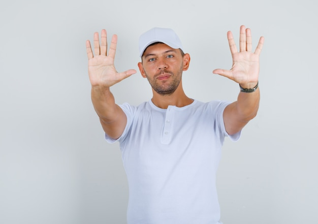 Young man showing palms to camera in white t-shirt, cap front view.