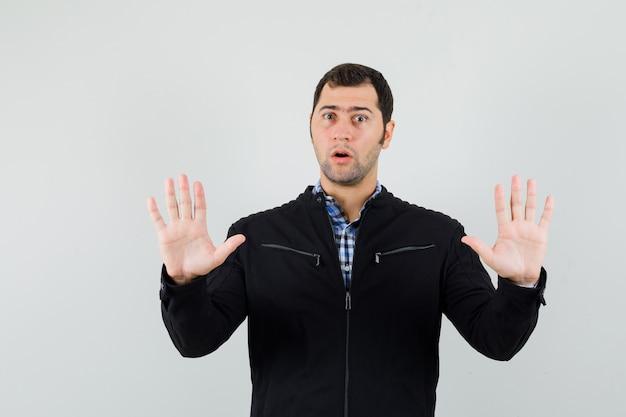 Молодой человек показывает ладони в жесте капитуляции в рубашке, куртке и выглядит обеспокоенным. передний план.