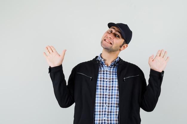Молодой человек показывает ладони в жесте капитуляции в рубашке, куртке, кепке и выглядит веселым, вид спереди.