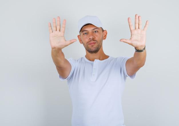 若い男が白いtシャツ、キャップのフロントビューでカメラに手のひらを示します。