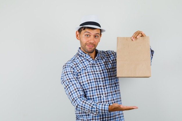 Young man showing paper bag in checked shirt