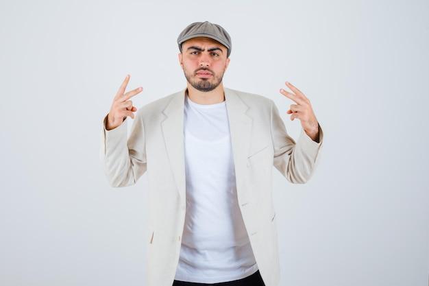 白いtシャツ、ジャケット、灰色の帽子でピースサインを示し、怒っているように見える若い男