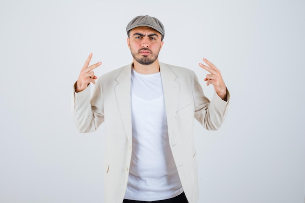 Young man showing peace signs in white t-shirt, jacket and grey cap and looking angry