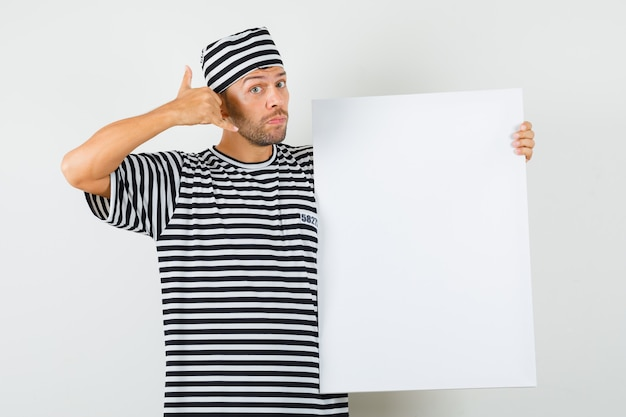 縞模様のtシャツ、帽子で空白のキャンバスを保持し、電話ジェスチャーを示す若い男。