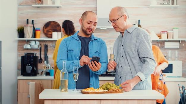 스마트폰으로 아버지에게 사진을 보여주는 젊은 남자. 현대적인 주방의 탁자에 둘러앉아 휴대전화를 사용하는 혼합 세대 사람들이 식사를 준비하는 동안 그룹입니다.