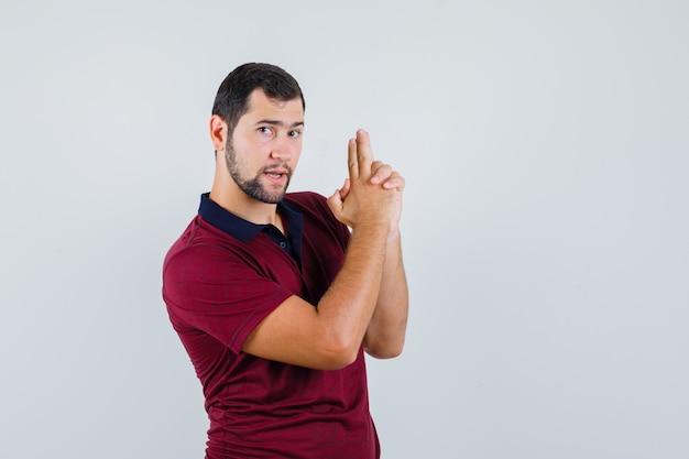 Giovane che mostra il segno della pistola in maglietta rossa e che sembra pronto, vista frontale.