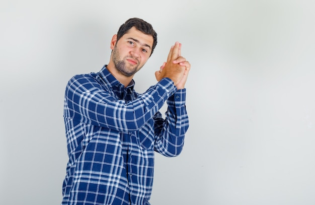 Young man showing pistol with hands in checked shirt and looking confident