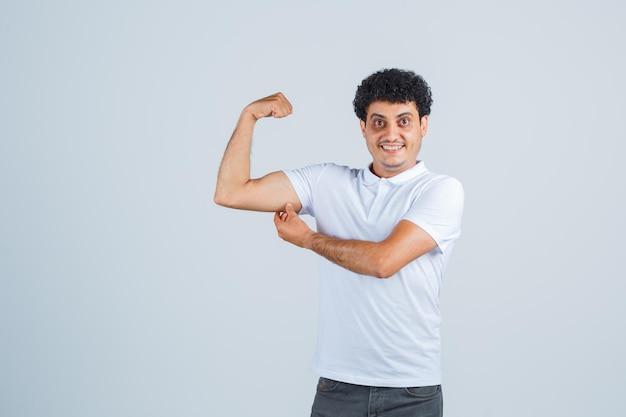 白いtシャツとジーンズで力のジェスチャーを示し、幸せそうに見える若い男。正面図。