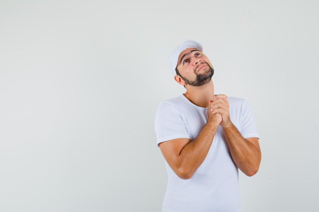 Young man showing praying gesture in t-shirt and looking impatient , front view. space for text