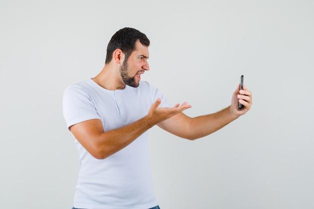 Giovane che mostra il gesto interrogativo mentre effettua la videochiamata in maglietta bianca e sembra pazzo.
