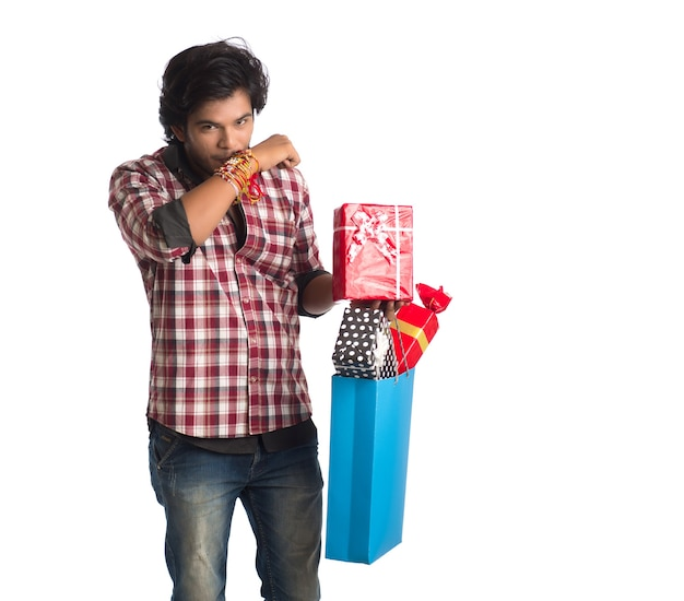 Young man showing rakhi on his hand with shopping bags and gift box on the occasion of raksha bandhan festival.