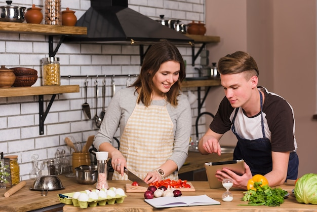 Young man showing recipe to cooking girlfriend