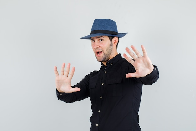 Young man showing refusal gesture in black shirt