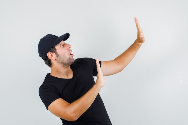 Young man showing refusal gesture in black t-shirt