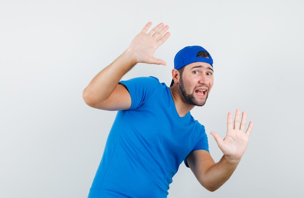 Young man showing refusal gesture in blue t-shirt and cap and looking frightened