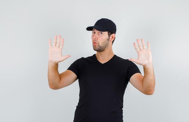 Молодой человек показывает жест отказа в черной футболке