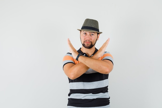 Молодой человек показывает жест отказа в футболке, шляпе и выглядит решительным.