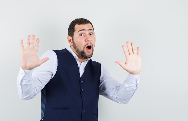 Young man showing refusal gesture in shirt and vest and looking scared