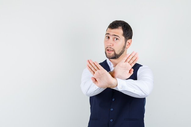 Young man showing refusal gesture in shirt and vest and looking serious