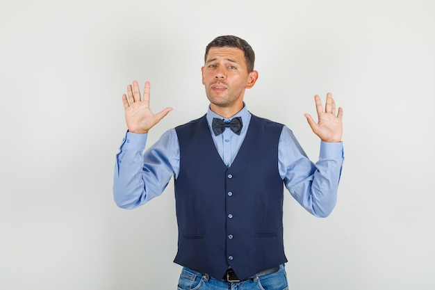 Young man showing refusal gesture in suit, jeans