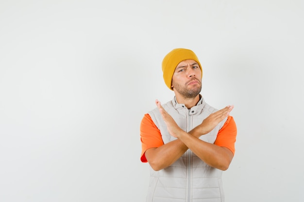 Young man showing refusal gesture in t-shirt, jacket, hat and looking resolute.