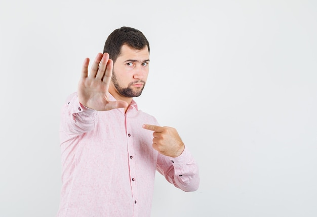Young man showing refusal gesture while pointing at himself in pink shirt and looking serious