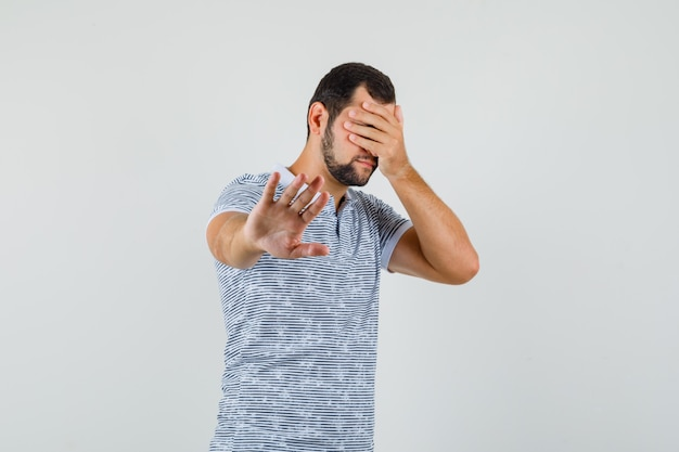 Young man showing refusal gesture with hand on eyes in t-shirt and looking scared , front view.