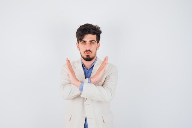 Giovane che mostra restrizione o gesto x in maglietta blu e giacca bianca e sembra serio