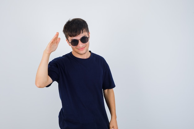 젊은 남자 검은 티셔츠에 경례 제스처를 보여주는 자신감, 전면보기를 찾고.