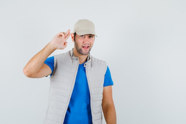 Young man showing salute gesture with fingers in t-shirt, jacket, cap and looking confident. front view.