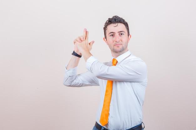 白いシャツ、ネクタイ、自信を持って射撃ジェスチャーを示す若い男