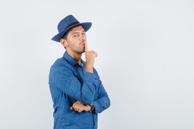 Giovane che mostra gesto di silenzio in camicia blu, cappello e sguardo attento. vista frontale.