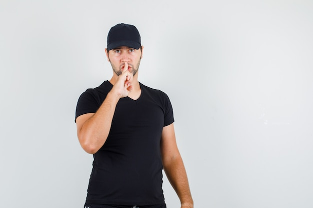 黒のtシャツで沈黙のジェスチャーを示す若い男