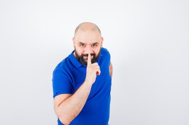 青いシャツで沈黙のジェスチャーを示し、集中して見える若い男、正面図。