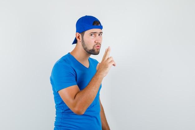 파란색 티셔츠와 모자에 침묵 제스처를 보여주는 젊은 남자와 조심스럽게보고