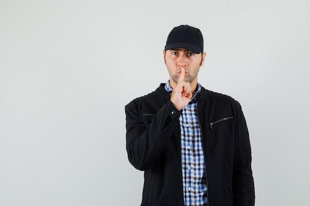 Молодой человек показывает жест молчания в рубашке, куртке, кепке и смотрит осторожно. передний план.
