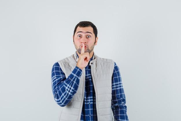 Молодой человек показывает жест молчания в рубашке, безрукавке и выглядит спокойным. передний план.