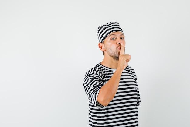 줄무늬 티셔츠, 모자에 침묵 제스처를 보여주는 젊은 남자와 조심스럽게 찾고.