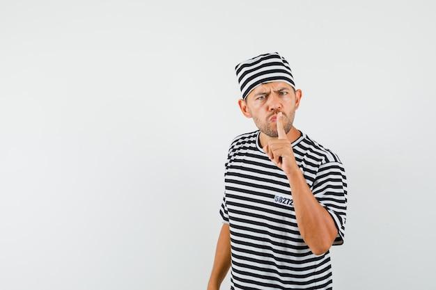 Молодой человек показывает жест молчания в полосатой футболке, шляпе и смотрит осторожно.