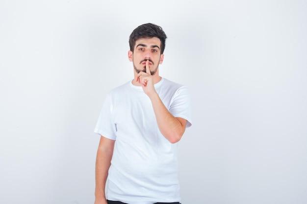 Молодой человек показывает жест молчания в белой футболке и выглядит уверенно