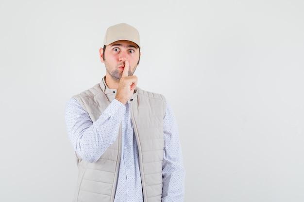 Giovane che mostra gesto di silenzio in camicia, giacca senza maniche, berretto e sembra serio, vista frontale.