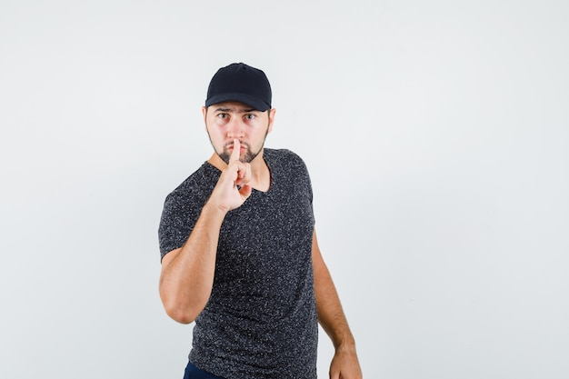 Young man showing silence gesture in t-shirt and cap and looking serious