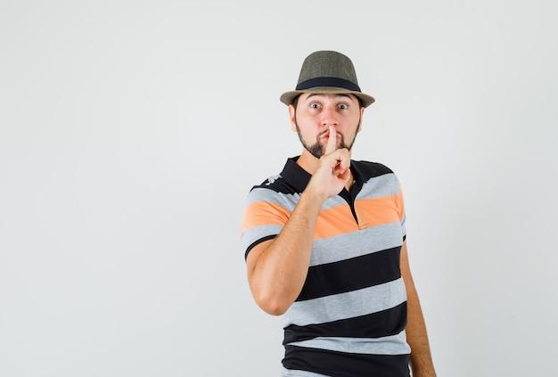 Giovane che mostra gesto di silenzio in maglietta, cappello e guardando attento