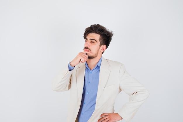 파란색 셔츠와 흰색 정장 재킷에 허리에 손을 잡고 잠겨있는 찾고있는 동안 침묵 제스처를 보여주는 젊은 남자
