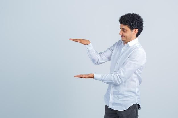 白いシャツ、ズボンでサイズのサインを示し、集中して見える若い男。正面図。