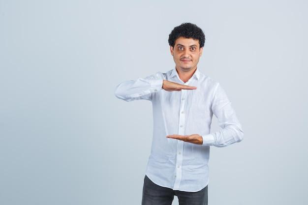 Il giovane che mostra la taglia firma in camicia bianca, pantaloni e sembra fiducioso, vista frontale.